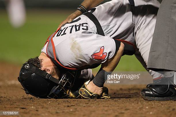Catcher Jarrod Saltalamacchia of the Boston Red Sox grimaces after being hit by a foul tip from the bat of Adam Jones of the Baltimore Orioles during...