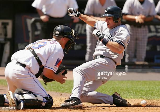 Catcher Jason Phillips of the New York Mets cannot hold onto the ball as John Flaherty of the New York Yankees slides into home for a run in the...