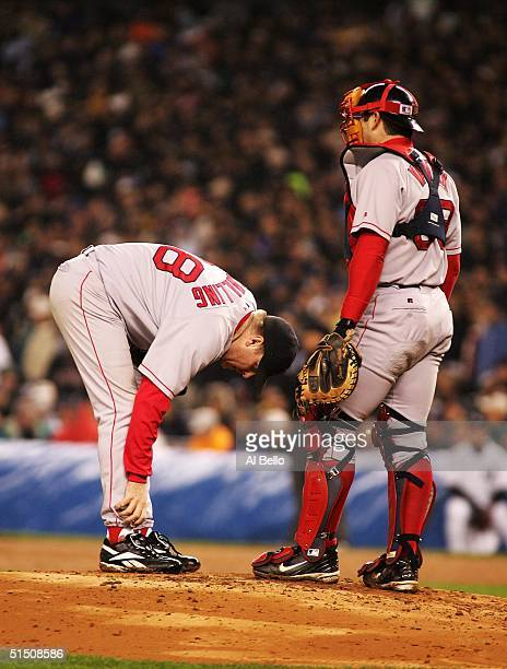 Catcher Jason Varitek of the Boston Red Sox approaches the mound as pitcher Curt Schilling looks at his ankle during game six of the American League...