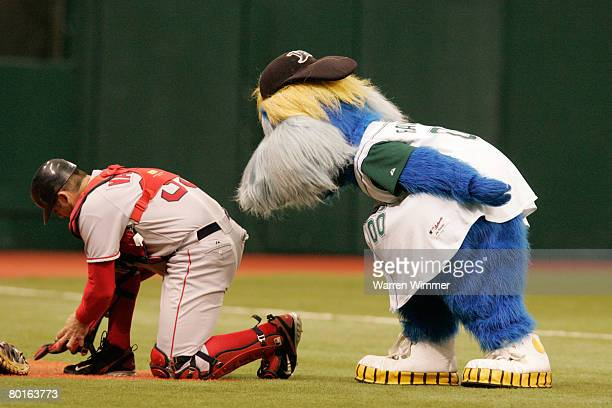 Catcher Jason Varitek of the Boston Red Sox is hassled by 'Raymond' the macot for the Devil Rays before the game between the Boston Red Sox and Tampa...