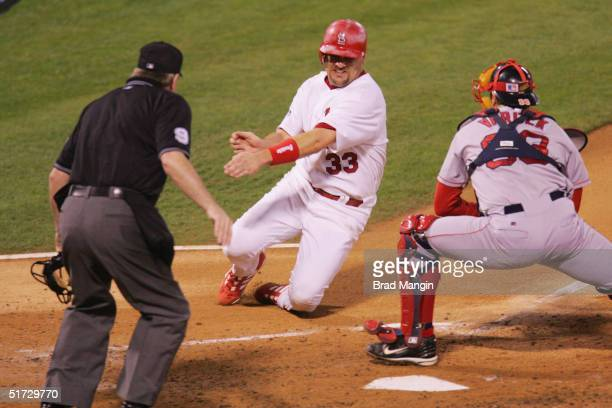Catcher Jason Varitek of the Boston Red Sox tags out Larry Walker of the St. Louis Cardinals at home plate in the first inning during game three of...