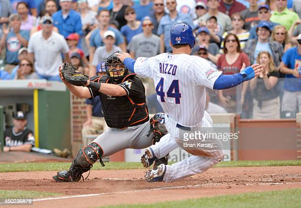 Catcher Jeff Mathis of the Miami Marlins gets ready to tag out Anthony Rizzo of the Chicago Cubs at home plate as Rizzo tries to score from first...