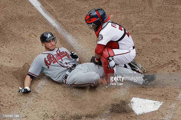 Catcher Jesus Flores of the Washington Nationals tags out Brandon Beachy of the Atlanta Braves trying to score at home plate during the fifth inning...
