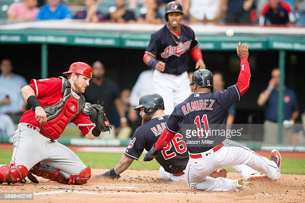 Catcher Jett Bandy of the Los Angeles Angels of Anaheim misses the catch as Mike Napoli and Jose Ramirez of the Cleveland Indians score on a double...