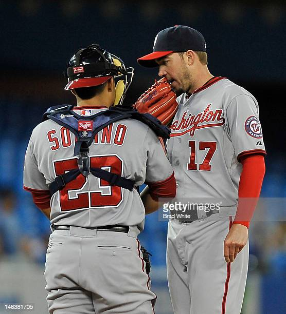 Catcher Jhonatan Solano of the Washington Nationals talks with relief pitcher Sean Burnett during interleague MLB game action against the Toronto...