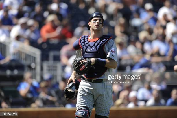 Catcher Joe Mauer of the Minnesota Twins looks to the first baseman to make the play on a foul pop fly during the game against the Kansas City Royals...