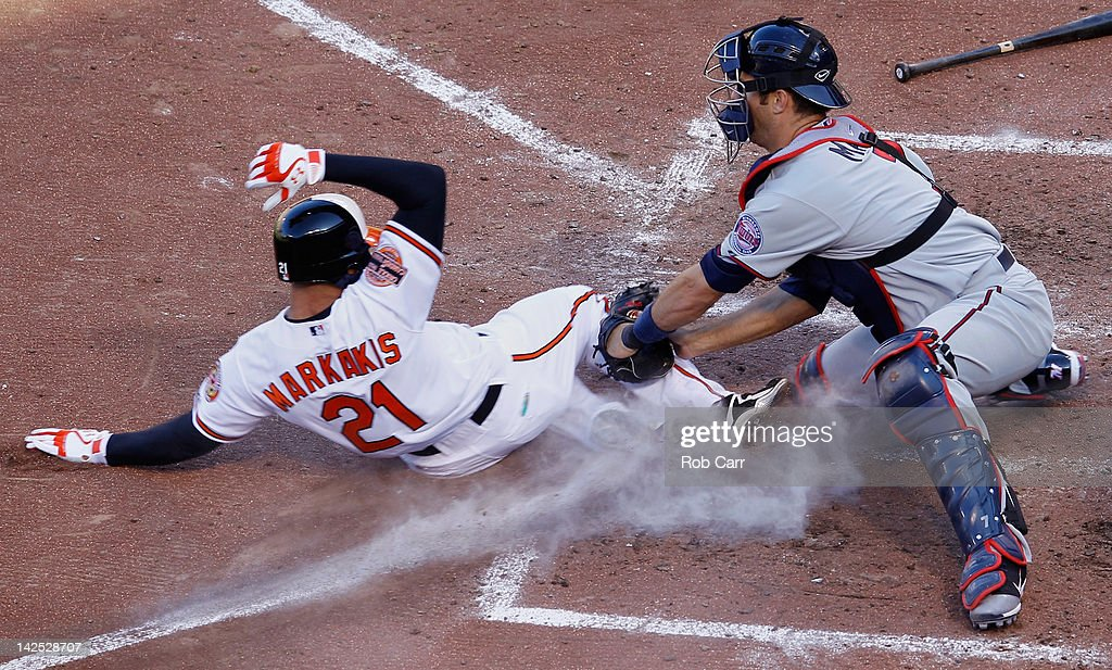 Catcher Joe Mauer #7 of the Minnesota Twins tags out Nick Markakis #21 of the Baltimore Orioles at the plate for the third out of the sixth inning during opening day at Oriole Park at Camden Yards on April 6, 2012 in Baltimore, Maryland.