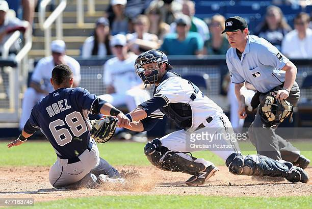 Catcher Jonathan Lucroy of the Milwaukee Brewers is unable to tag out Rico Noel of the San Diego Padres as he slides in to score on an insidethepark...