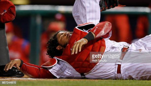 Catcher Jorge Alfaro of the Philadelphia Phillies is knocked over by Juan Lagares of the New York Mets who attempted to score on a fly ball by Travis...