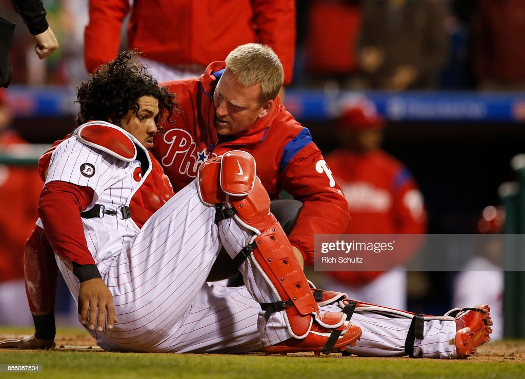 Catcher Jorge Alfaro #38 of the Philadelphia Phillies is looked after by trainer Scott Sheridan. Alfaro was knocked over by Juan Lagares #12 of the New York Mets who attempted to score on a fly ball by Travis d'Arnaud #18 during the sixth inning of a game at Citizens Bank Park on September 30, 2017 in Philadelphia, Pennsylvania.