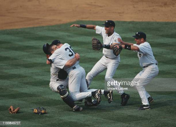 Catcher Jorge Posada embraces David Cone pitcher for the New York Yankees and celebrates with team mates Derek Jeter and Chuck Knoblauch after...