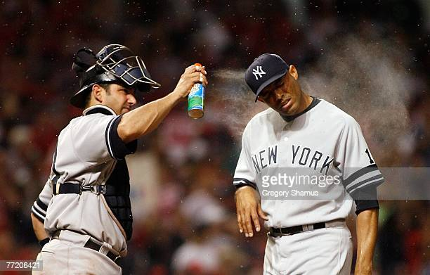 Catcher Jorge Posada of the New York Yankees sprays relief pitcher Mariano Rivera with bug spray as gnats swarm around the pitchers mound against the...
