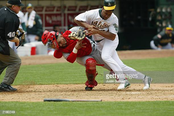 Catcher Jose Molina#28 of the Anaheim Angels is knocked down as he tries to tag Jermaine Dye of the Oakland Athletics during the MLB game at the...