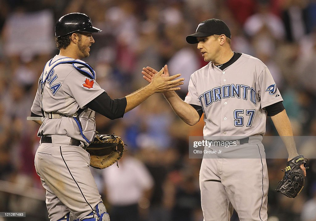 Catcher J.P. Arencibia #9 of the Toronto Blue Jays celebrates with Shawn Camp #57 after defeating the Seattle Mariners 13-7 at Safeco Field on August 16, 2011 in Seattle, Washington.
