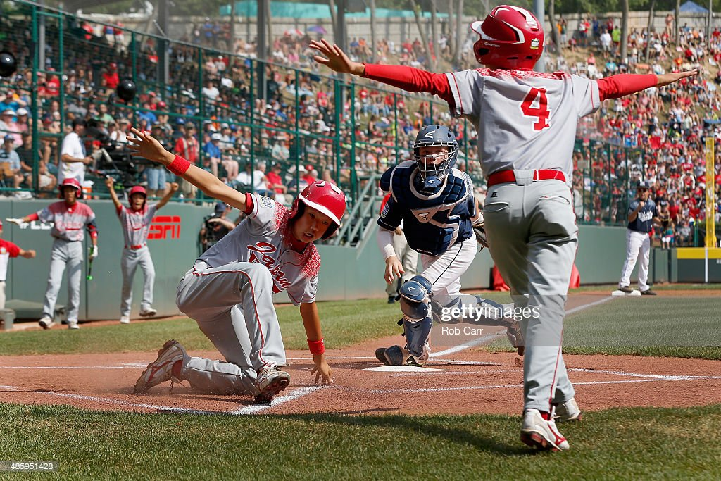 Catcher Kaden Peifer #16 of the Mid-Atlantic team from Red Land Little League of Lewisberry, Pennsylvania looks on as Shingo Tomita #10 of team Japan scores a run in front of teammate Yugo Aoki #4 in the first inning of the Little League World Series Championship game at Lamade Stadium on August 30, 2015 in South Willamsport, Pennsylvania.
