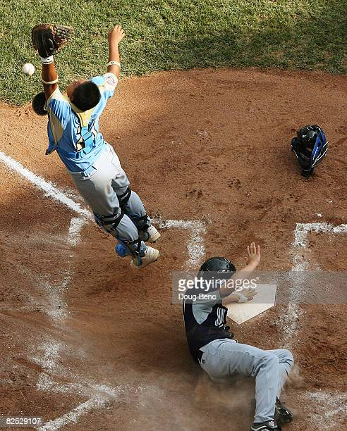 Catcher Keelen Obedoza of the West goes can't bring down an errant throw as Beau Jordan of the Southwest crosses the plate for a run during the...