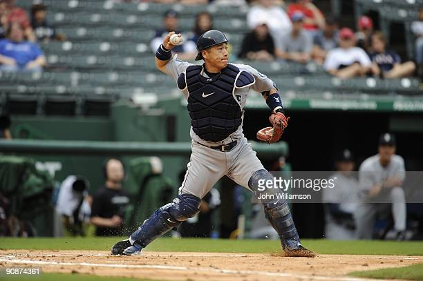 Catcher Kenji Johjima of the Seattle Mariners fields his position as he throws to second base after picking up a ball hit in front of home plate...