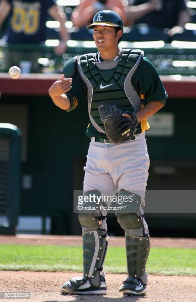 Catcher Kurt Suzuki of the Oakland Athletics warms up before the spring training game against the San Francisco Giants at Scottsdale Stadium on March...