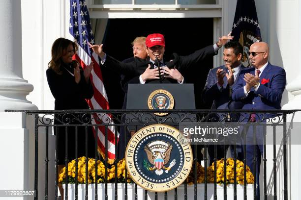 Catcher Kurt Suzuki wears a Make America Great Again hat as he is hugged by US President Donald Trump as he welcomes the 2019 World Series Champions...
