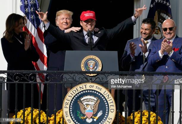 Catcher Kurt Suzuki wears a Make America Great Again hat as he is embraced by US President Donald Trump as he welcomes the 2019 World Series...