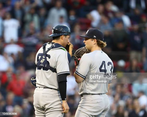 Catcher Kyle Higashioka of the New York Yankees meets Pitcher Chance Adams of the New York Yankees on the mound as he joins the game in the bottom of...
