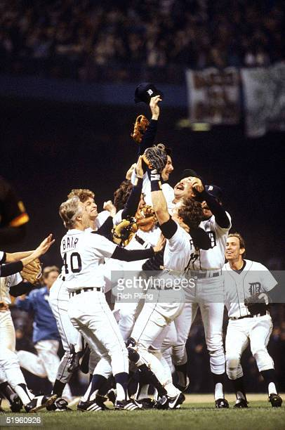 Catcher Lance Parrish of the Detroit Tigers holds up teammate pitcher Wille Hernandez as the Tigers celebrate on the field after winning game 5 of...