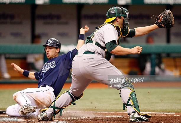 Catcher Landon Powell of the Oakland Athletics gets the throw as Ben Zobrist of the Tampa Bay Rays scores during the game at Tropicana Field on July...