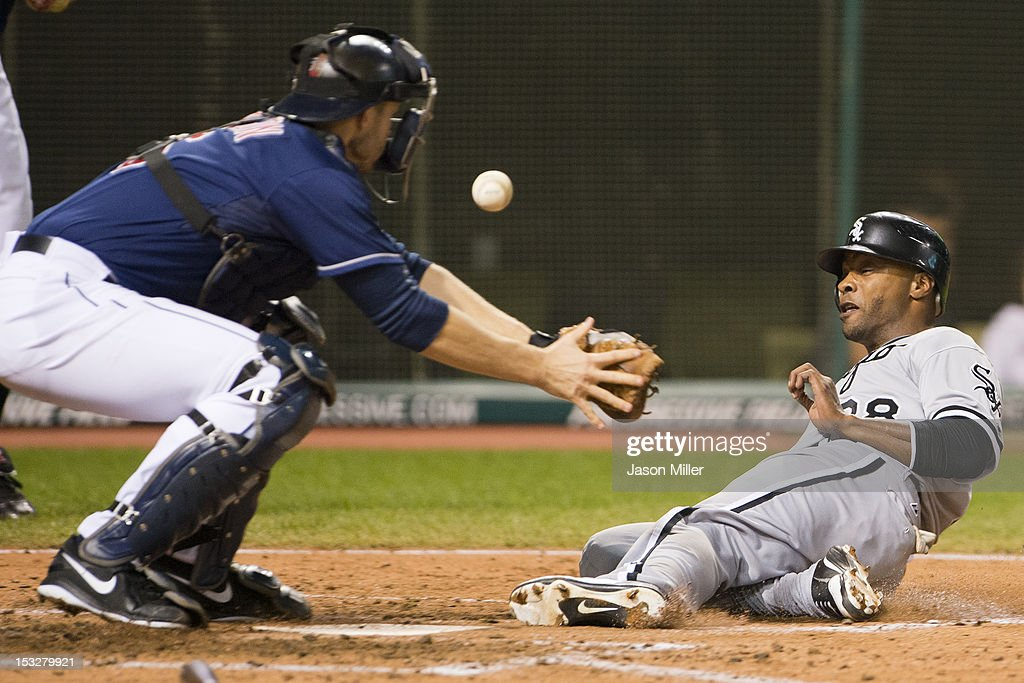 Catcher Lou Marson #6 of the Cleveland Indians misses the catch as Dewayne Wise #28 of the Chicago White Sox is safe at home off a hit by Orlando Hudson #5 during the sixth inning at Progressive Field on October 2, 2012 in Cleveland, Ohio.