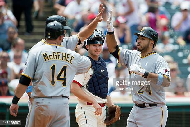 Catcher Lou Marson of the Cleveland Indians watches as Casey McGehee and Garrett Jones celebrate with Pedro Alvarez of the Pittsburgh Pirates after...