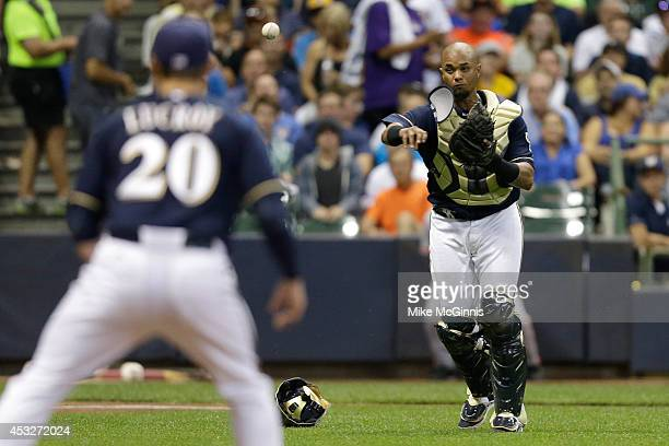 Catcher Martin Maldonado of the Milwaukee Brewers makes the throw to first base to retire Ryan Vogelsong of the San Francisco Giants during the top...