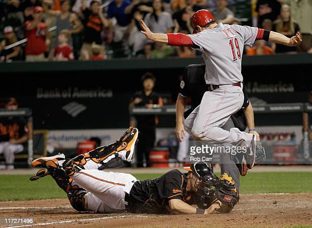Catcher Matt Wieters of the Baltimore Orioles tags out Joey Votto of the Cincinnati Reds trying to score at home plate for the third out during the...