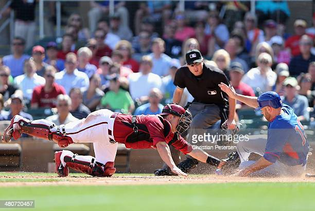 Catcher Miguel Montero of the Arizona Diamondbacks attempts to tag Nate Schierholtz of the Chicago Cubs at home plate as he slides in to sccore a run...