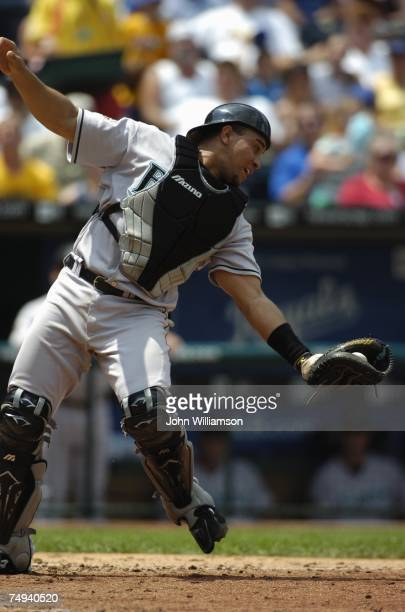Catcher Miguel Olivo of the Florida Marlins fields his position as he catches a pop fly in front of home plate during the game against the Kansas...