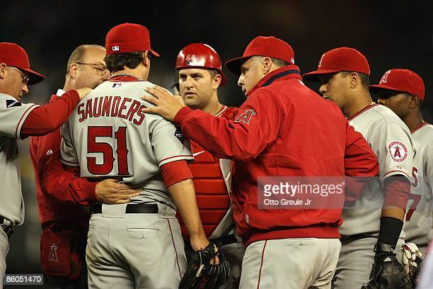 Catcher Mike Napoli and manager Mike Scioscia attend to pitcher Joe Saunders of the Los Angeles Angels of Anaheim during the game against the Seattle...