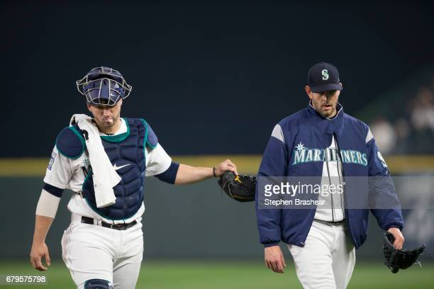 Catcher Mike Zunino left of the Seattle Mariners and starting pitcher James Paxton of the Seattle Mariners walks to the dugout before a game against...