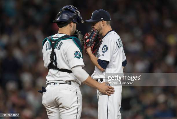 Catcher Mike Zunino of the Seattle Mariners and relief pitcher Casey Lawrence of the Seattle Mariners meet at the pitchers mound during a game...