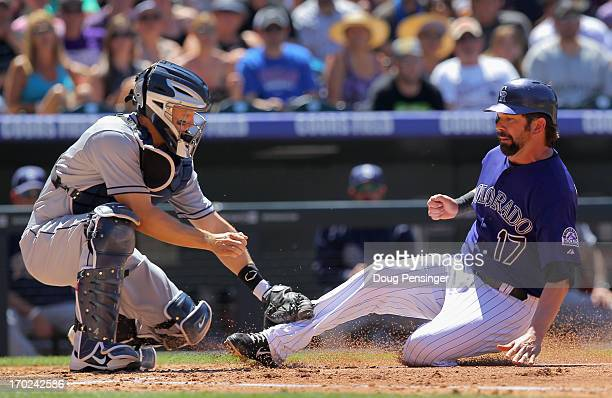 Catcher Nick Hundley of the San Diego Padres tags out Todd Helton of the Colorado Rockies at home as he tries to score on a fly ball by Jonathan...