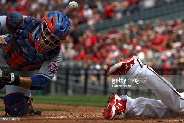 Catcher Rene Rivera of the New York Mets cannot make the tag on Anthony Rendon of the Washington Nationals as he scores during the first inning at...