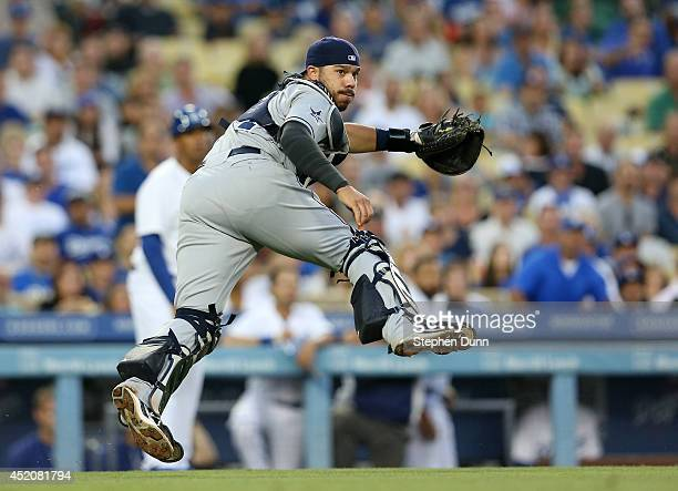 Catcher Rene Rivera of the San Diego Padres watches as his throw to first gets Dee Gordon of the Los Angeles Dodgers trying to bunt for a base hit in...