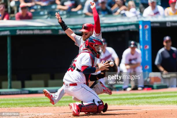 Catcher Roberto Perez of the Cleveland Indians makes the catch as Kole Calhoun of the Los Angeles Angels of Anaheim scores to tie the game during the...