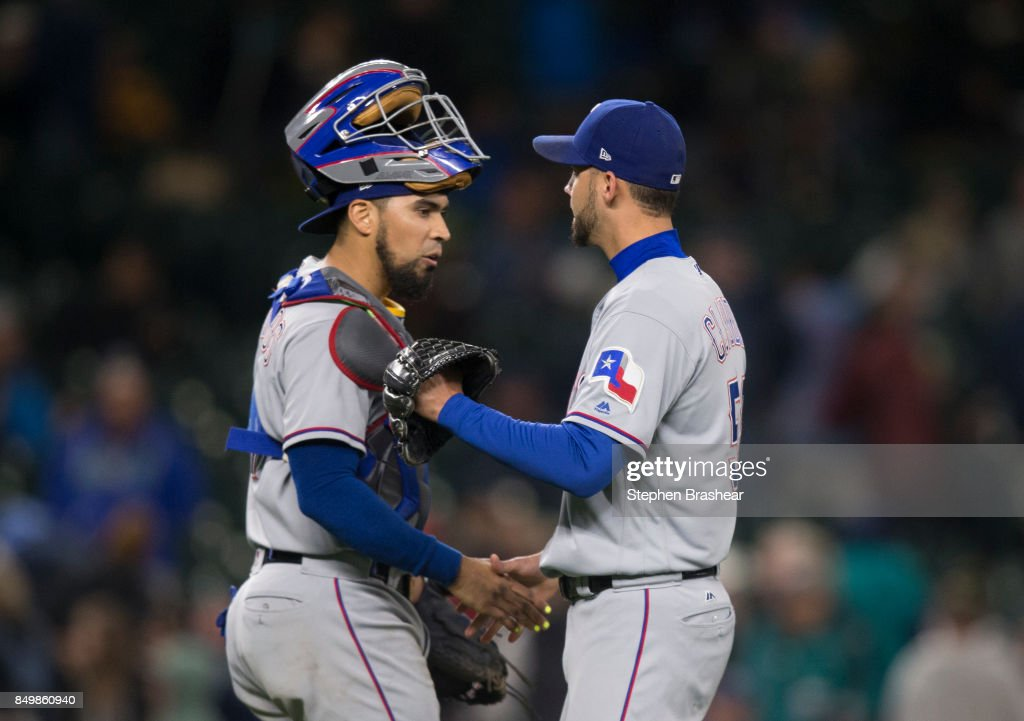 Catcher Robinson Chirinos #61 of the Texas Rangers and relief pitcher Alex Claudio #58 of the Texas Rangers celebrate after a game against the Seattle Mariners at Safeco Field on September 19, 2017 in Seattle, Washington. The Rangers won the game 3-1.