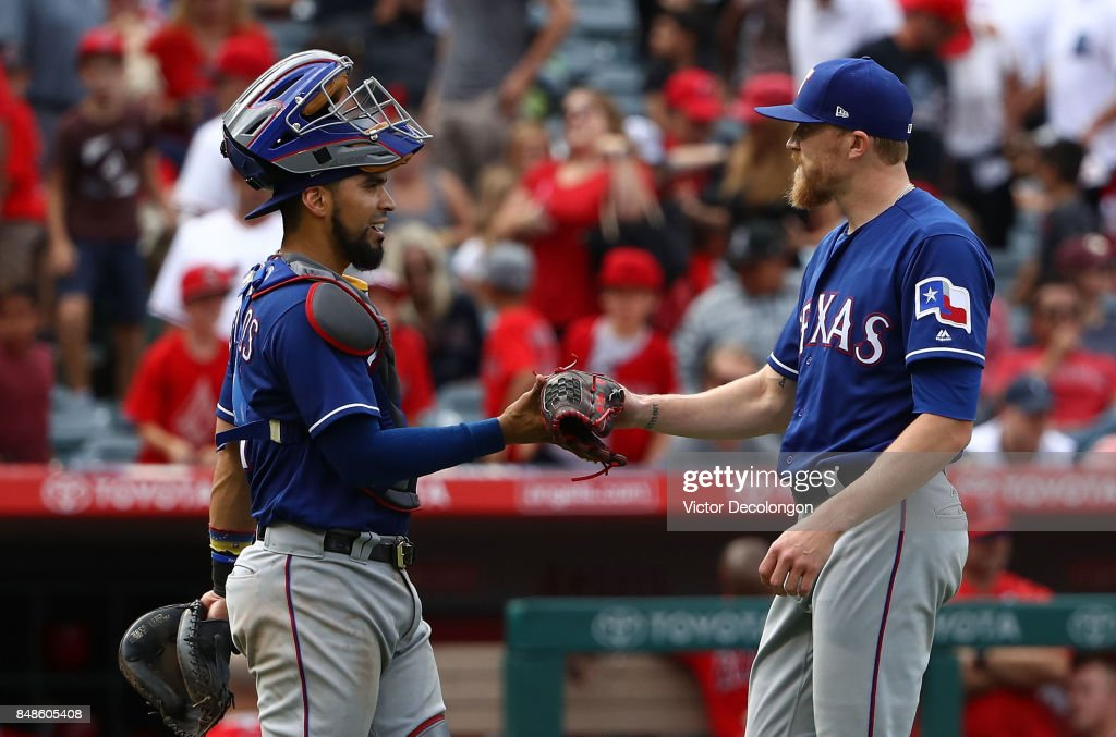 Catcher Robinson Chirinos #61 of the Texas Rangers congratulates closing pitcher Jake Diekman #41 after closing out the game for a 4-2 win against the Los Angeles Angels of Anaheim in their MLB game at Angel Stadium of Anaheim on September 17, 2017 in Anaheim, California.