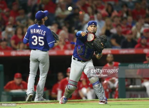 Catcher Robinson Chirinos of the Texas Rangers throws to first in front of pitcher Cole Hamels to get Albert Pujols of the Los Angeles Angels of...