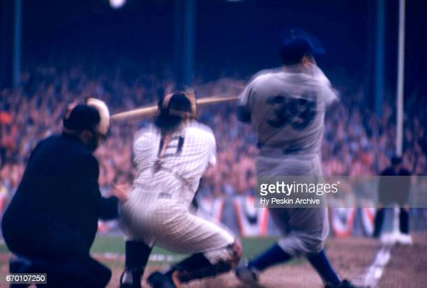 Catcher Roy Campanella of the Brooklyn Dodgers swings at a pitch as catcher Yogi Berra of the New York Yankees looks to catch the ball during a 1955...