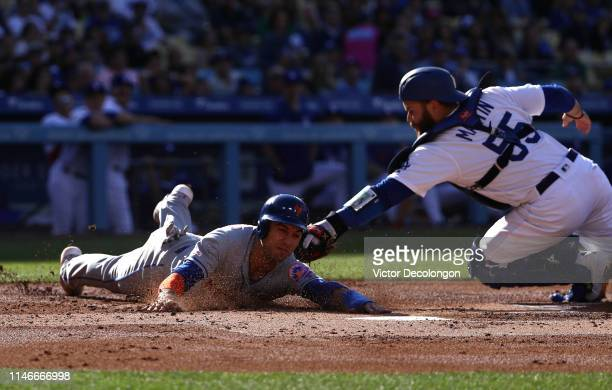 Catcher Russell Martin of the Los Angeles Dodgers gets the tag down in time for the out at home plate on Michael Conforto of the New York Mets in the...