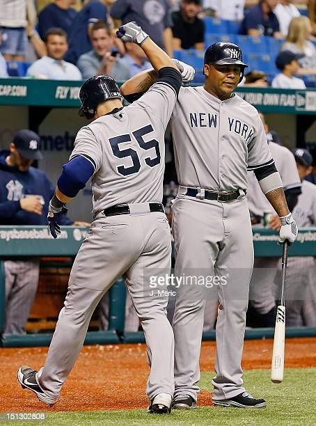 Catcher Russell Martin of the New York Yankees is congratulated by Andruw Jones after his home run against the Tampa Bay Rays during the game at...
