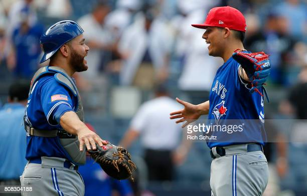 Catcher Russell Martin of the Toronto Blue Jays and closer Roberto Osuna celebrate their 41 win over the New York Yankees during a game at Yankee...