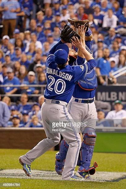 Catcher Russell Martin of the Toronto Blue Jays catches a ball alongside Josh Donaldson to end the sixth inning against the Kansas City Royals in...