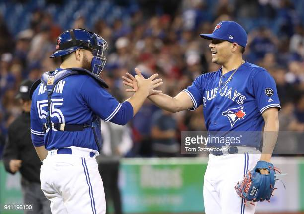 Catcher Russell Martin of the Toronto Blue Jays celebrates a win over the Chicago White Sox with Roberto Osuna at Rogers Centre on April 2 2018 in...