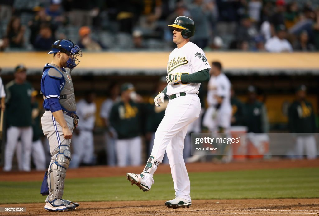 Catcher Russell Martin #55 of the Toronto Blue Jays watches Ryon Healy #25 of the Oakland Athletics cross home plate after he hit his second home run of the night in the fourth inning at Oakland Alameda Coliseum on June 5, 2017 in Oakland, California.